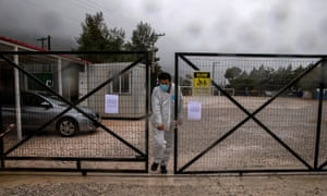 A man wearing a protective suit and a face mask exits the Malakasa migrant camp after authorities found a coronavirus case and placed the camp under quarantine, following the outbreak of coronavirus in Malakasa, Greece, 5 April 2020.